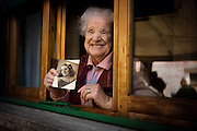 An elderly woman at her windowsill reminisces  of her younger years.