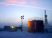 Alaska.  North Slope.  Kuparuk Oilfield.  Wellhouse at dusk with drilling rig and airplane condensate trail in background.