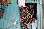 Two youngsters peek out of their house.  The slum of Cheetah Camp on the outskirts of Mumbai, India is a predominantly muslim community on living on the fringe while the city continues to grow.