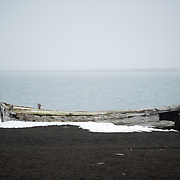 A wooden whaling boat sits on the beach at Whalers Bay on Deception Island. A whaling station once occupied the site, which is now abandoned. Deception Island, in the South Shetland Islands, is a caldera of a volcano and is comprised of volcanic rock.