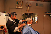 Barber, Juan Alcala-Casillas, cuts Ron Hitzeman's hair at Billy's Barber Shop in Tucson, Arizona, USA, on February 14th, 2012, the date of the 100th birthday of the state of Arizona.  The shop, located on South Mission Road, has been in business for 25 years.  Hitzman says that he especially likes the hot lather.