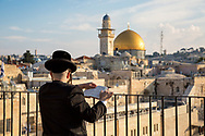 Jewish man reciting the Torah early in the morning. In the background the Dome of the Rock.