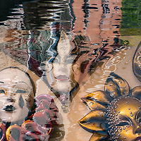Carnival masks super imposed on water reflections