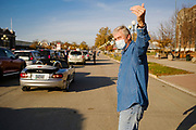 06 NOVEMBER 2020 - DES MOINES, IOWA: A volunteer directs traffic during an emergency food distribution at the Iowa State Fairgrounds Friday. A spokesperson for the Food Bank of Iowa said they had enough food for 1,500 families. Each family got frozen chicken legs, frozen liquid eggs, and fresh produce. There will be another emergency food distribution at the Fairgrounds on November 30. Food insecurity in the Des Moines area has skyrocketed since the start of the Coronavirus pandemic. Although unemployment rates in Iowa have fallen since a peak in June, many families that fell behind on rent are now facing eviction. The food bank spokesperson said use of the Food Bank's emergency pantries and distribution points is still increasing.    PHOTO BY JACK KURTZ