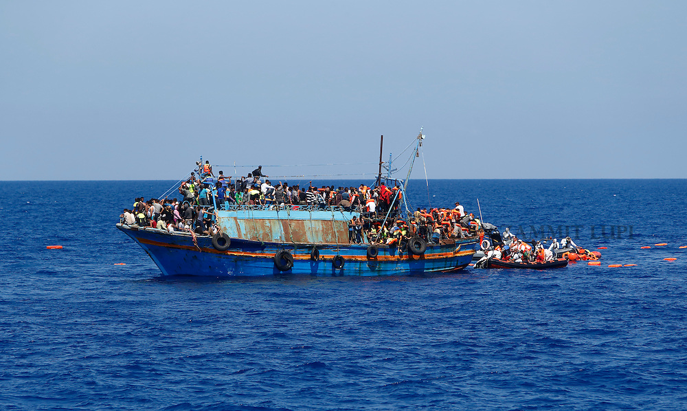 Migrants on board an overloaded wooden boat are rescued off the coast of Libya August 6, 2015.  An estimated 600 migrants on the boat were rescued by the international non-governmental organisations Medecins san Frontiere (MSF) and the Migrant Offshore Aid Station (MOAS) without loss of life on Thursday afternoon, a day after more than 200 migrants are feared to have drowned in the latest Mediterranean boat tragedy after rescuers saved over 370 people from a capsized boat thought to be carrying 600.<br /> REUTERS/Darrin Zammit Lupi <br /> MALTA OUT. NO COMMERCIAL OR EDITORIAL SALES IN MALTA
