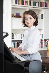 Portrait of girl playing piano, smiling
