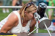 Middletown, New York - A woman watches a partial solar eclipse through a telescope with a solor filter on Alumni Green at SUNY Orange on Aug. 21, 2017.