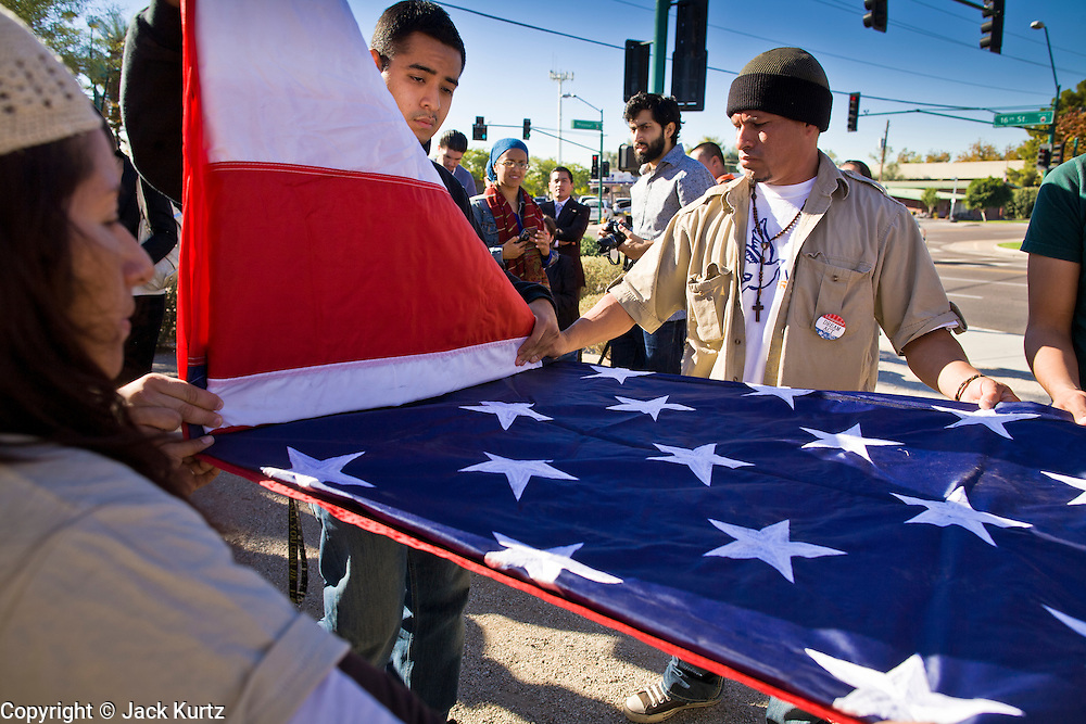"""07 DECEMBER 2010 - PHOENIX, AZ:  Supporters of the DREAM Act fold up an American flag after picketing the offices of US Sen. John McCain in Phoenix Tuesday. Dolores Huerta, who started working in the civil rights movement in the 1960's, threw her support behind students fasting on behalf of the DREAM Act in front of Sen. John McCain's office Tuesday. The student picked McCain's office because he used to support the DREAM Act. They hope that the US Senate will pass the DREAM Act during its """"lame duck"""" session. The Senate debated and defeated similar legislation just before the November general election.   PHOTO BY JACK KURTZ"""