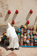 A man stacks hats that are for sale from his shop in the medina of Essaouira, Morocco