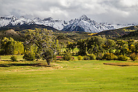 Open ranchland below the snow covered 14,150 ft. Mount Sneffels of the Sneffels Range.   San Juan Mountains, Colorado.