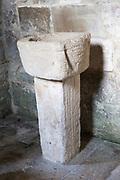 Simple stone baptismal christening font Saxon church of Saint Laurence, Bradford on Avon, Wiltshire, England, UK probably built circa 1000 AD
