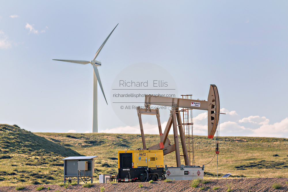 A wind turbine next to a oil pump jack operating at the Happy Jack Wind Farm outside Cheyenne, Wyoming.