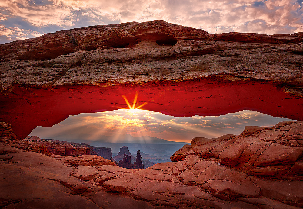 Sunrise crepuscular rays burst onto the landscape behind Mesa Arch in Canyonlands National Park.