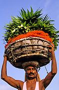 INDIA, CALCUTTA, PEOPLE, Flower market at Jagannath Ghat and man with head basket (Kolkata)