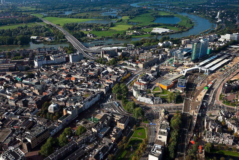Nederland, Gelderland, Arnhem, 03-10-2010; Nederrijn en centrum van de stad, hoofdkantoren van Essent en ingenieursbureau Arcadis (rechts) rond de bouwput van het centraal station. Aan de overzijde van rivier de Neder-Rijn de uiterwaard en polder Meinerswijk, links de Mandelabrug. Het gehele stationsgebied Arnhem Centraal wordt opnieuw ingericht, het station zelf wordt herbouwd..Downtown Arnhem with headquarters Essent and engineering firm Arcadis (right), next to the the building site from the central station. On the other side of the Rhine River floodplain and polder Meinerswijk. The whole station area of Arnhem Central is refurbished, the station itself rebuilt.luchtfoto (toeslag), aerial photo (additional fee required).foto/photo Siebe Swart