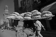 Egypt . Cairo : bread sellers, street life in Gamaliyya area in front of the Khanqah of Sultan Baybars al Gashankir and minaret   Islamic Cairo .NM32