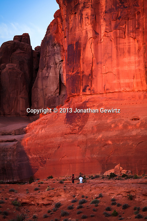 Rock formations whose red color is accentuated by morning sunlight tower over visitors in Arches National Park, Utah. WATERMARKS WILL NOT APPEAR ON PRINTS OR LICENSED IMAGES.<br /> <br /> Licensing: https://tandemstock.com/assets/88023192