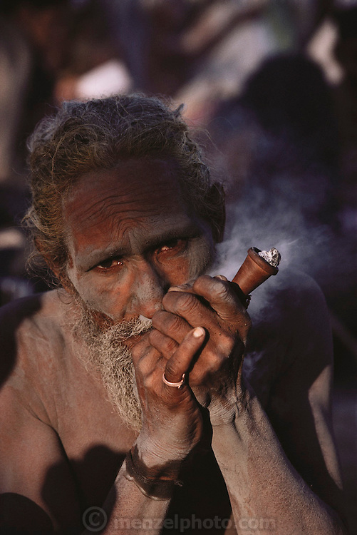 Portrait of a naga who is smoking hash and tobacco in a clay chillum pipe at Kumbh Mela.  Every 12 years, millions of devout Hindus celebrate the month-long festival of Kumbh Mela by bathing in the holy waters of the Ganges at Hardiwar, India. Hundreds of ashrams set up dusty, sprawling camps that stretch for miles. Under the watchful eye of police and lifeguards, the faithful throng to bathe in the river.