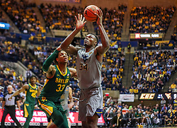 Mar 7, 2020; Morgantown, West Virginia, USA; West Virginia Mountaineers forward Oscar Tshiebwe (34) makes a move around Baylor Bears forward Freddie Gillespie (33) during the second half at WVU Coliseum. Mandatory Credit: Ben Queen-USA TODAY Sports