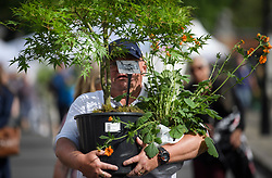 © Licensed to London News Pictures. 25/05/2019. London, UK. Members of the public carry exhibitors' plants from the 2019 Chelsea Flower show which ended today (Sat). A wide array of unusual and striking display items can be purchased on the closing day of The Royal Horticultural Society flagship flower show, held at the Royal Hospital in Chelsea since 1913. Photo credit: Ben Cawthra/LNP