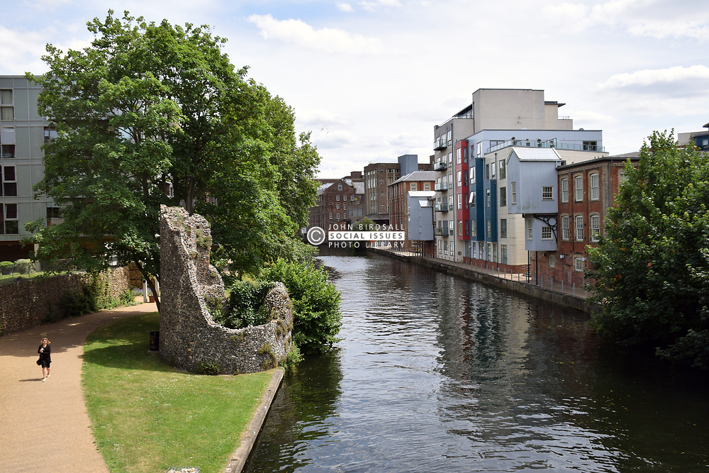 New housing developments on bank of River Wensum, Norwich UK 2017. On site of old Colman factory. Remains of city walls in foreground