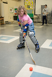Primary school pupil learning how to play inline hockey during a rollerblading lesson at school,