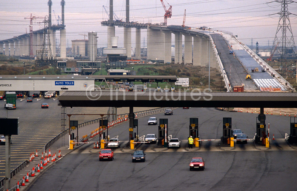 An aerial landscape at the Dartford Bridge crossing of dated 1990 before the completion of London's newest Thames river crossing - the Queen Elizabeth II Bridge. Already used are the toll booths taking much-needed toll fees from motorists as they emerge from the pre-existing Dartford Tunnel (1963). The Bridge is a 137 m (449 ft) high and 812 m (2,664 ft) long cable-stayed road bridge across the River Thames in south east England. It was opened in 1991 by Queen Elizabeth II. It is the southbound element of the Dartford Crossing, a strategic congestion charged road crossing the half mile wide river east of London. It was built alongside two earlier tunnels under the Thames, which now form the northbound element of the crossing. Upon completion, the bridge was Europe's largest cable-supported bridge.