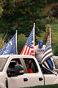 26 SEPTEMBER 2020 - DES MOINES, IOWA: Pro-Trump flags on vehicles at the pro-Trump motorcade starting point at Farm Boy Garage. More than 1,500 people in 500 vehicles participated in motorcade through Des Moines Saturday. They started in the suburbs south of downtown, drove through downtown, and ended at the State Capitol.        PHOTO BY JACK KURTZ
