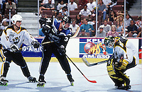 1996:  Bullfrogs goalie Rob Laurie stops a puck from LA Blades player during a Roller Hockey International RHI indoor inline hockey game.  Original image scan from negative, print or  transparency.  Image is available for personal or editorial use only.   BJ MacPherson hooking Blades player.