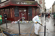 Cleaning up blood and mess in front of Le Carillon, Corner of Rue Bichat and Rue Aubert<br />