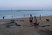 Hours after the tragic drowning of a young woman in the water on the Norfolk coast, beach visitors stare out to sea, on 9th August 2020, in Sea Palling, Norfolk, England.