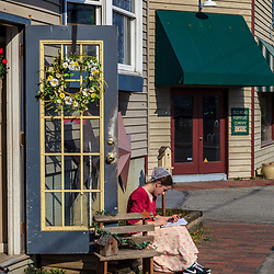 Intercourse, PA, USA - March 13, 2012: A Mennonite woman reads a book outside her shop in Intercourse, PA.