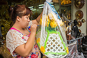 """12 NOVEMBER 2012 - BANGKOK, THAILAND:   A store clerk prices a pre made alms basket for sale in a shop on Bamrung Muang Street in Bangkok. Thanon Bamrung Muang (Thanon is Thai for Road or Street) is Bangkok's """"Street of Many Buddhas."""" Like many ancient cities, Bangkok was once a city of artisan's neighborhoods and Bamrung Muang Road, near Bangkok's present day city hall, was once the street where all the country's Buddha statues were made. Now they made in factories on the edge of Bangkok, but Bamrung Muang Road is still where the statues are sold. Once an elephant trail, it was one of the first streets paved in Bangkok. It is the largest center of Buddhist supplies in Thailand. Not just statues but also monk's robes, candles, alms bowls, and pre-configured alms baskets are for sale along both sides of the street.    PHOTO BY JACK KURTZ"""