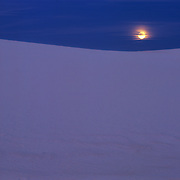 Glowing gypsum dunes under the full moon in White Sands National Park, New Mexico.