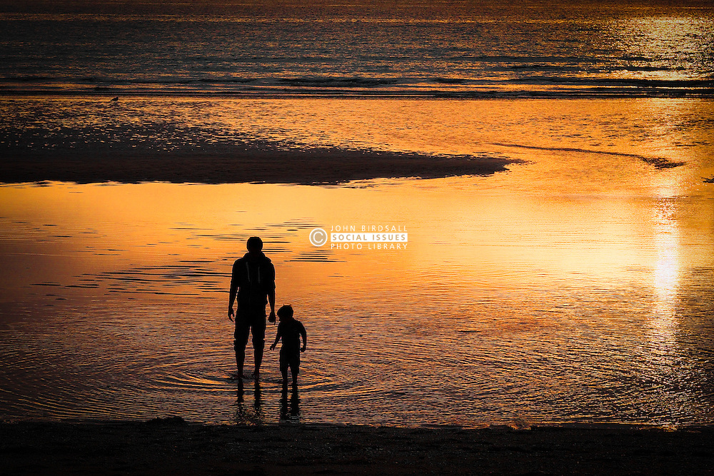 A father and son exploring the beach at Fistral in Newquay, Cornwall.