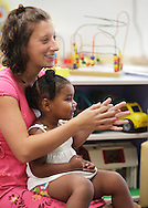 Aviana Diaz-Brown sits on the lap of Infant-toddler teacher Melanie Heller during a sing-along as Lisa Munoz, right, looks on during the Early Head Start Program at Sullivan County Head Start in Woodbourne on Tuesday, July 23, 2013.