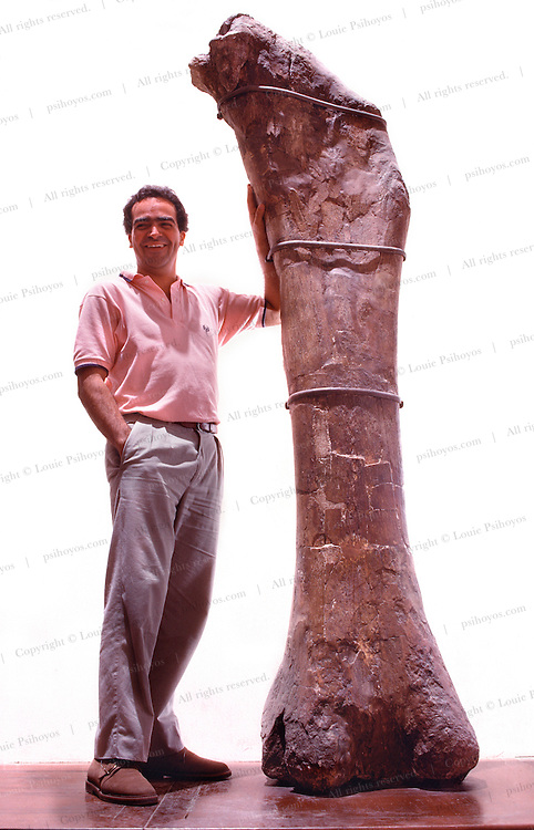 At the Museum of La Plata University in Argentina, paleontologist Fernando E. Novas stands next to a femur of Antarctosaurus, a giant titanosaur sauropod of the Late Cretaceous which may have weighed up to fifty tons.