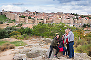 Tourists taking a selfie photograph using smartphone at famous Avila medieval city walls, UNESCO World Heritage Site, Spain