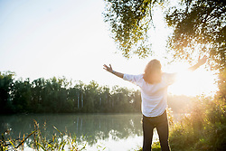 Rear View of man with arms outstretched against sunlight by river, Bavaria, Germany