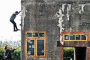 Nederland, Zeeuws Vlaanderen, Groede, 12-9-2019 .Een kind klimt op een Duitse bunker uit de tweede wereldoorlog . Deze was onderdeel van de Atlantik Wall, de kustverdediging van noordwest europa tegen een invasie .Bij Groede ligt het zgn bunkerdorp, een aantal bunkers die militairem huisvesten die twee kanonnen bedienden en in opleiding waren. De betonnen kazematten werden door hen beschilderd met ramen en gordijnen als camouflage zodat het gewone huizen leken. Nu gebruken kinderen ze om op te klimmen en is het nepdorpje een museum, oorlogsmuseum.Foto:Flip Franssen