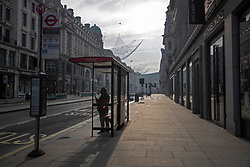 © Licensed to London News Pictures. 08/11/2020. London, UK. A man waits at a bus stop on a quiet Regent Street in Central London. A national lockdown has been put in place in an attempt to fight a second wave of the COVID-19 strain of Coronavirus. Photo credit: George Cracknell Wright/LNP