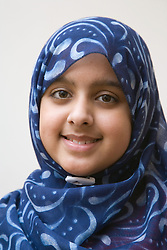 Young Asian girl; wearing a hijab; smiling,