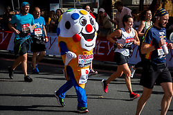 © Licensed to London News Pictures. 03/10/2021. LONDON, UK. A runner in an ice cream costume on Embankment passes mile 25 in the London Marathon, the first time it has been held since April 2019 due to the Covid-19 pandemic.  Over 36,000 elite athletes, club runners and fun runners are taking part in the mass event, with another 40,000 people taking part virtually.  Photo credit: Stephen Chung/LNP