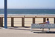 Nederland, Scheveningen, 20-6-2019 Aan de boulevard zit een oudere vrouw op een bankje naar het strand te kijken . Foto: Flip Franssen
