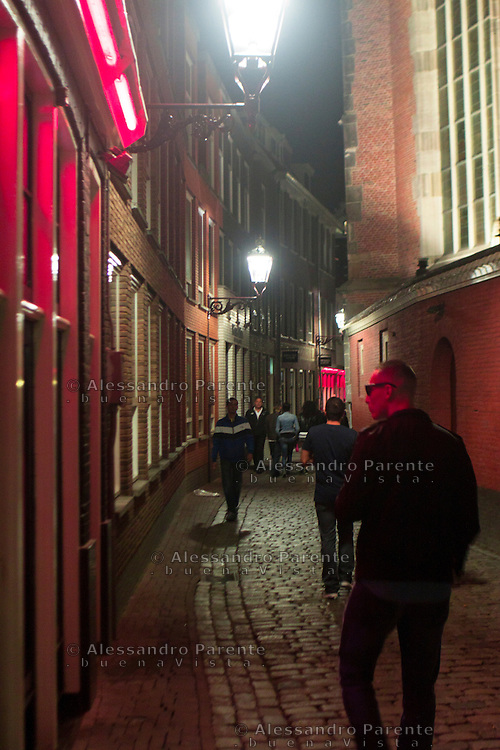 a tourist waching through a red light district window in Amsterdam.