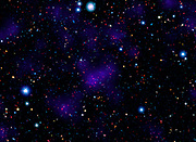 A surprisingly large collection of galaxies stands out at a remarkably large distance in this composite image combining infrared and visible-light observations. Spitzer.