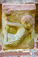Norman Romanesque exterior corbel no 47  - sculpture of a a bald dancing female dressed in a tight filling tunic. The image is probably a warning against the sexual senses that can be aroused by dancing. The figure has her legs crossed and appears to be recoiling from an impending violation. The Norman Romanesque Church of St Mary and St David, Kilpeck Herefordshire, England. Built around 1140 .<br /> <br /> Visit our MEDIEVAL PHOTO COLLECTIONS for more   photos  to download or buy as prints https://funkystock.photoshelter.com/gallery-collection/Medieval-Middle-Ages-Historic-Places-Arcaeological-Sites-Pictures-Images-of/C0000B5ZA54_WD0s