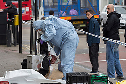 © licensed to London News Pictures. London, UK 11/05/2013. A forensic officer investigating a crime scene where a man found stabbed on Tottenham High Road. The man reported to be in a critical condition and seven people have been arrested. Photo credit: Tolga Akmen/LNP