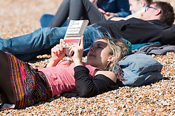 © Licensed to London News Pictures. 25/03/2016. Brighton, UK.  A woman reads a book as Thousands of people relax in the sun on Brighton Beach at the start of the Easter Bank Holliday weekend. Photo credit: Hugo Michiels/LNP