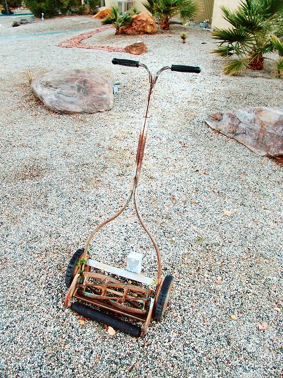 Rusty lawn mower parked in a front yard paved with stones.
